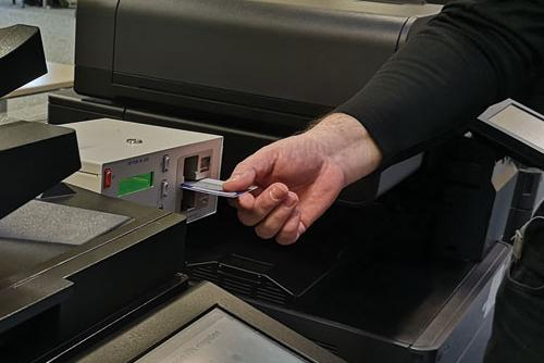 A hand putting the UniCard into a slot of a printer.