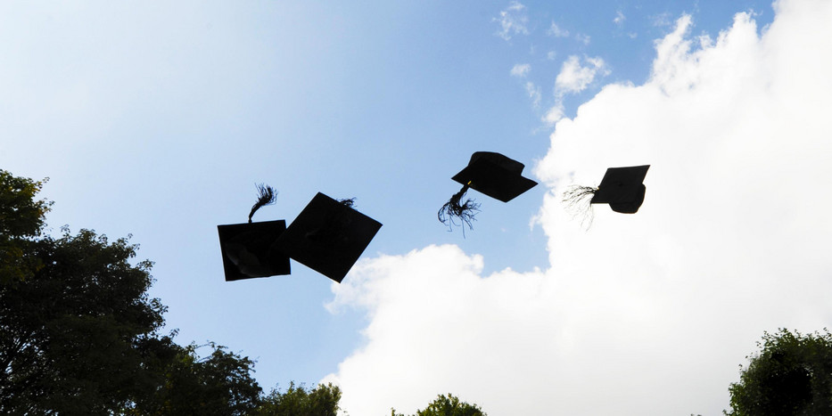 Four doctoral caps thrown into the air