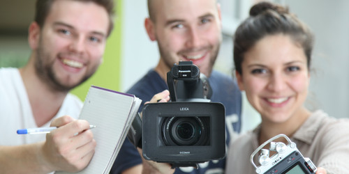 Two young men and one young woman with a notebook, a video camera and an audio recorder
