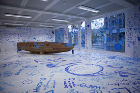 A painted wooden boat in a room with white walls and blue graffiti on them.