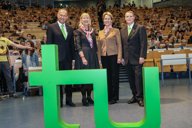 "Group photo of two women and two men in a large auditorium full of people. In front of them there is a very large green ""TU"" logo sculpture."