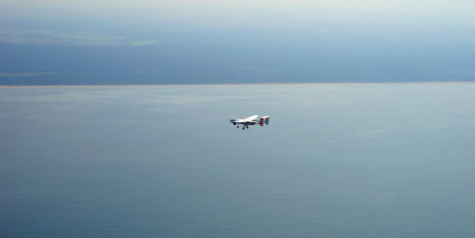 A small airplane above the sea.