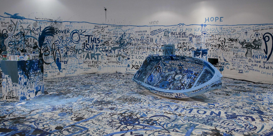 A large white room with words written in blue all over the walls and the floor. in the middle there is ablue boat.