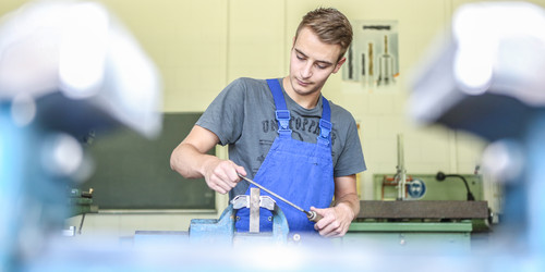 A young man in a blue overall working at a workbench.