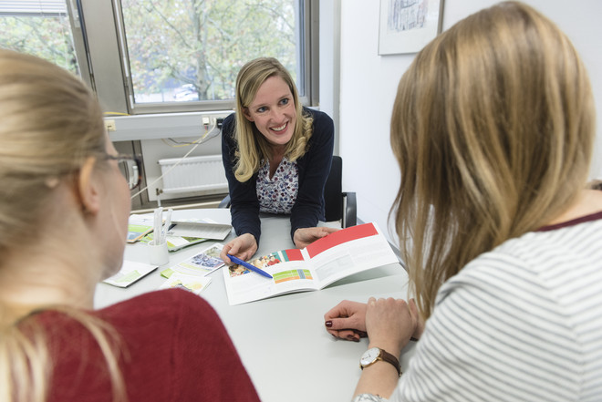 Two blond female students sitting at a desk in front of a smiling woman who holds an open brochure in her hands