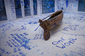 A painted wooden boat in a white room painted with blue color.