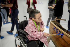 A woman sitting in a wheelchair is painting the word hope on a wooden boat.