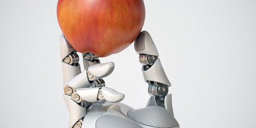 A robot's arm is holding an apple