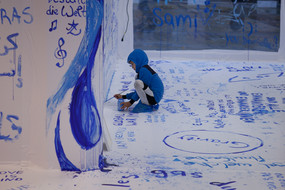 A child is painting a white wall with blue color.