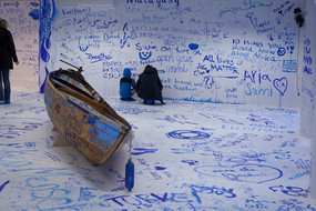 A painted room with a wooden boat and people painting the walls with blue color.