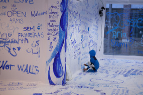 A child is painting a wall with a brush and blue color.