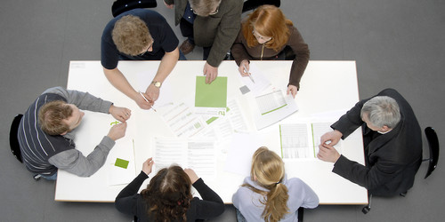 Photo of a group of people sitting at a desk, viewed from above