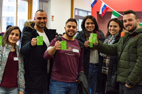 A group of international students holding green TU Dortmund University coffee cups