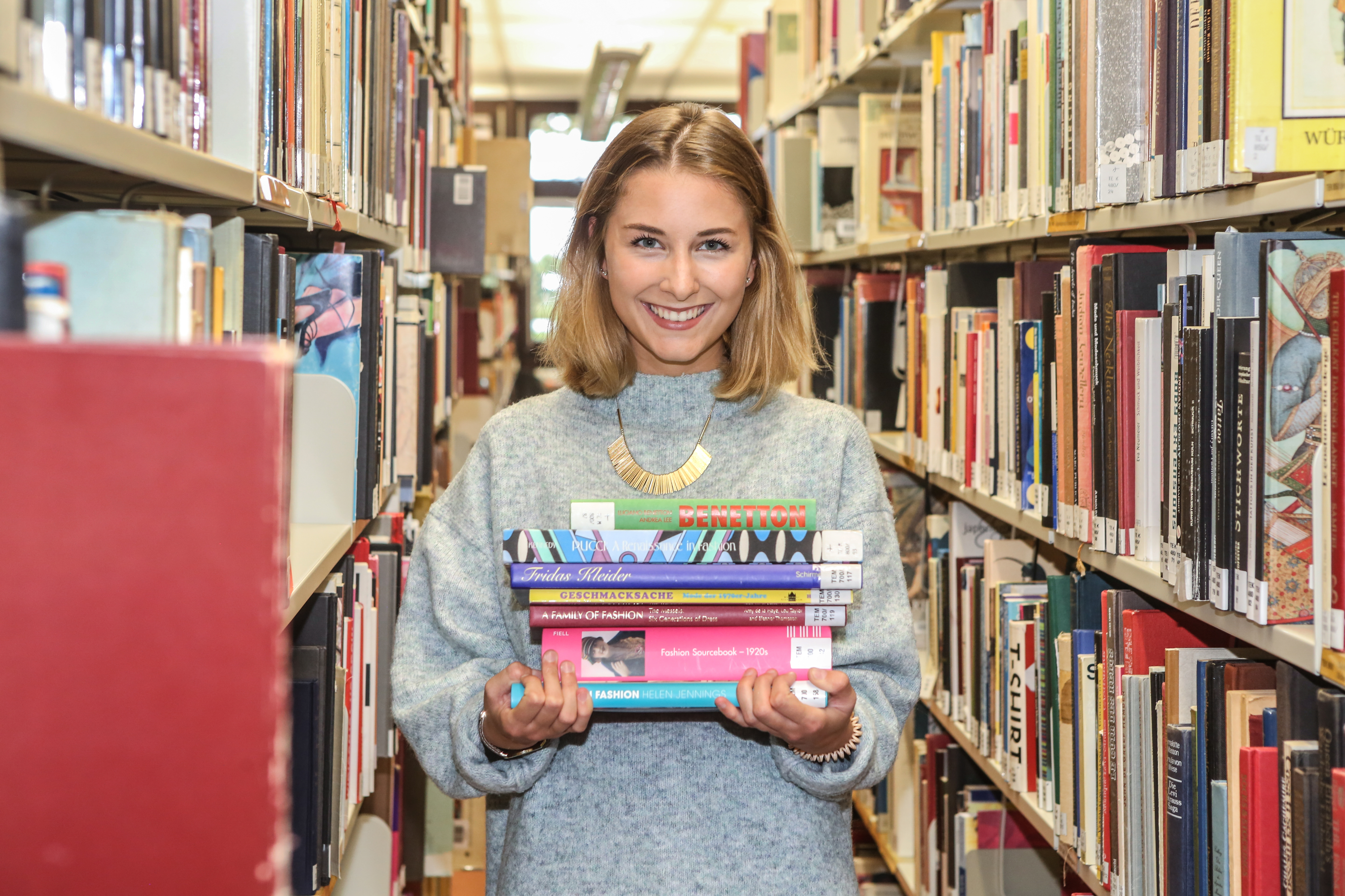 female student in the university library with books in her hands