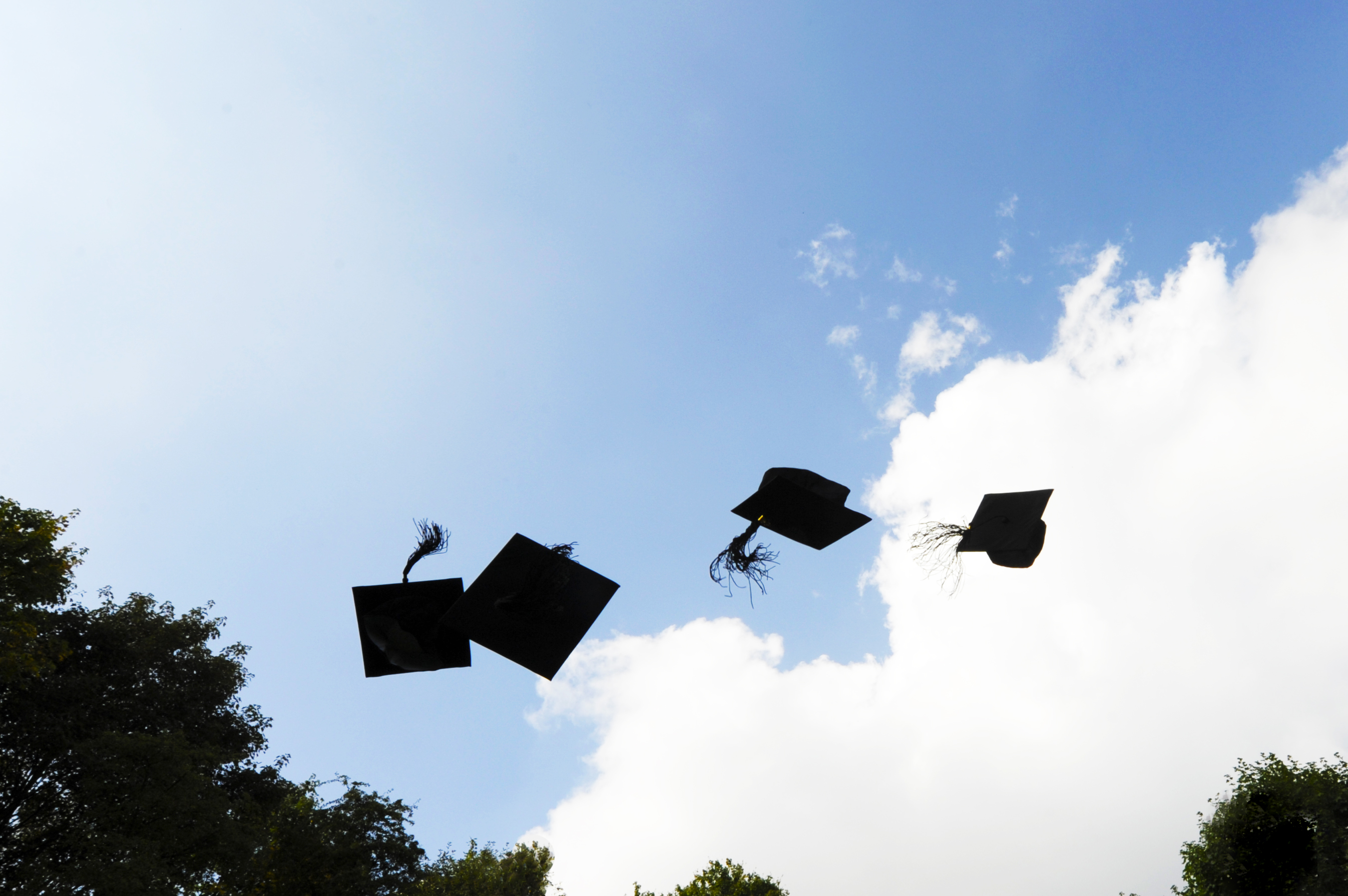 Four black graduation caps are thrown in the air.