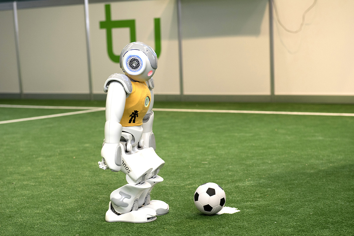 A yellow and white robot with a football