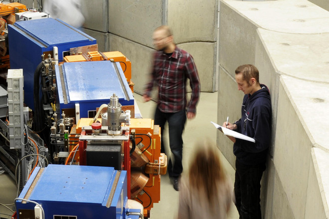 Indoor shot of three persons doing research at the electron storage ring DELTA