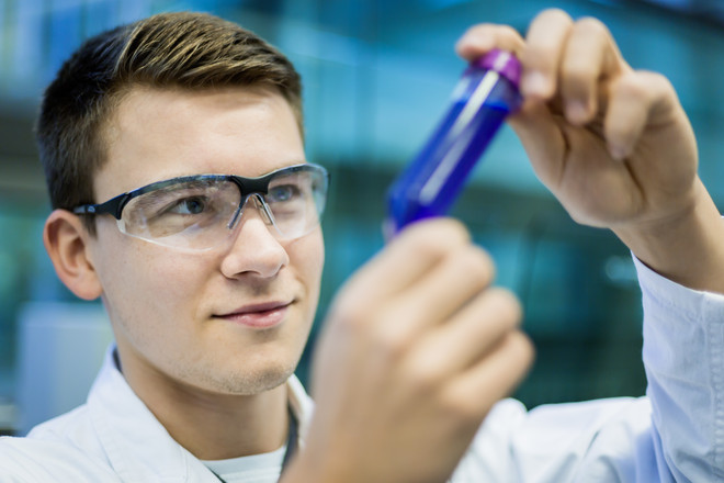 A male student wearing safety glasses holds a test tube with a blue liquid in his hands.