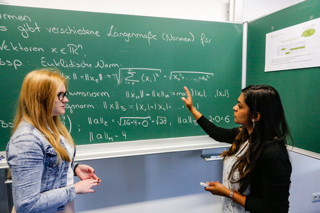 Two young women in front of a blackboard with mathematical formula