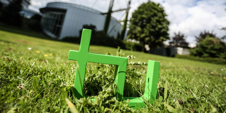 A green sculpture of the TU Dortmund University logo in the grass. In the background, you can see the Audimax and Math Tower buidling.