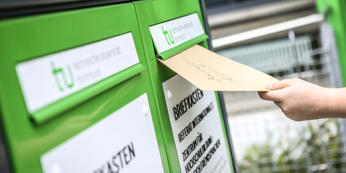 A letter is thrown into a light green post box with the TU Dortmund University logo.