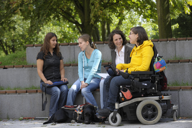 Four women sitting outside on the campus, two of them with a white cane, one of them in a wheelchair