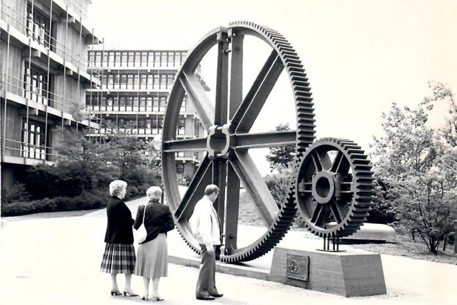 Historical black and white photo of three people looking at the big sculpture of industrial cogwheels on Campus North