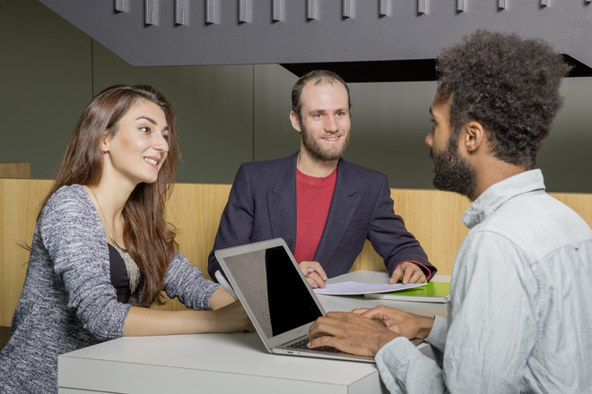 Three students sitting at a table and talking with each other