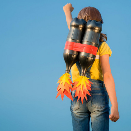 Viewed from behind: A young person carrying a dummy of a jetpack on its back and raising the left fist into the blue sky
