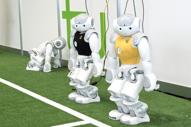 Three small white robots, one in a black jersey, one in a yellow jersey, standing next to a indoor soccer field with the green TU logo in the background.